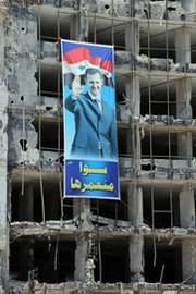 "A banner seen in the Syrian city of Homs on Tuesday shows President Bashar Assad alongside the Arabic-language slogan, ""We build it together."" Assad's government is reportedly under international pressure to explain discrepancies between its declared chemical-warfare assets and separate findings."
