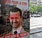 A poster seen in Paris on Monday displays criticism of Syrian President Bashar Assad. France said physical indications of chlorine-gas strikes by Syria's government may not definitively prove that Damascus used the chemical as a weapon.
