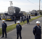 Japanese police guard a mixed-oxide fuel shipment in 2009. Japan reportedly did not inform U.N. regulators for two years of a plutonium fuel cache sitting idle in one of its reactors.