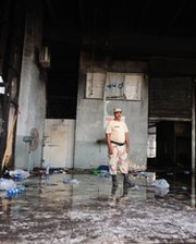 A Pakistani security official stands guard at the fire-damaged premises of a cold-storage cargo facility at the Jinnah International Airport in Karachi on Tuesday, a day after a terrorist attack at the site.