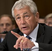 U.S. Defense Secretary Chuck Hagel, shown testifying before a Senate subcommittee on Tuesday, said the Pentagon plans to substantially scale back use of private support contractors (AP Photo/Scott Applewhite).