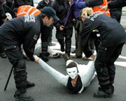 A demonstrator is arrested by police during a 2005 protest against nuclear weapons in front of NATO headquarters in Brussels. Language inserted into a House defense spending bill would require the Pentagon to report on how the alliance pays for keeping tactical nuclear weapons in Europe.