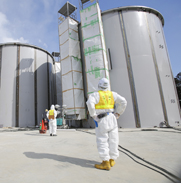 A worker looks at radioactive-water storage tanks under construction in March at Japan's Fukushima Daiichi nuclear power plant. Japan plans this year to consider ratifying a treaty that would shift any nuclear-accident liability to the operators of atomic facilities.