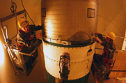 Workers inspect a Minuteman 3 intercontinental ballistic missile in 2002 at Malmstrom Air Force Base in Montana. The U.S. Air Force finished modifying its long-range nuclear missiles to each carry just one warhead.