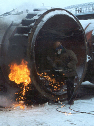 A worker cuts into a ballistic missile submarine launch tube in a destruction effort supported by the Cooperative Threat Reduction program. While most Defense Department work in Russia will cease with the expiration of the program's implementing deal, many Energy Department security projects in Russia will continue, a senior Obama administration official said on Thursday (U.S. Defense Threat Reduction Agency photo).