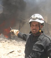 A Syrian rescue worker points toward a burning building after an alleged Syrian army airstrike in Aleppo earlier this month. The Obama administration on Thursday said it is seeking $500 million for a new Pentagon program to train and equip rebels in Syria.