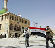 Syrian government fighters hold their nation's flag for a photo in a village north of Damascus on Tuesday. The world's chemical-arms watchdog on Tuesday said an international disarmament effort will be very active this month as work continues to remove all such Syrian materials by the end of June.