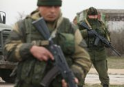 Troops under Russian command occupy the Crimean Peninsula's Belbek air base on Tuesday. The United States on Monday suspended its military collaboration with Russia in a sign of escalating tensions between the world's two largest nuclear powers.