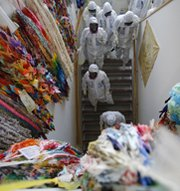 Technicians and journalists walk along a wall lined with paper cranes on Monday at Japan's Fukushima Daiichi nuclear power plant. More than a dozen nations revamped domestic atomic safety measures in response to damage sustained by the Japanese facility following an earthquake and tsunami three years ago, the U.S. Government Accountability Office said.