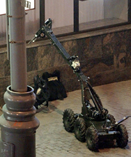 A robot lifts a rucksack containing a bomb shortly before it exploded in downtown Moscow, circa July 2003. Russia plans to field robots this year to guard its nuclear-armed missile sites.