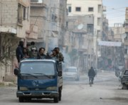 Syrian opposition fighters ride a truck through the town of Deir Ezzor on Monday. Rockets this week reportedly struck a Syrian coastal city where President Bashar Assad's government is turning over chemical-warfare materials for destruction by other governments.