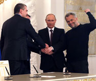 Russian President Vladimir Putin, center, joins hands with senior Crimean government officials in the Kremlin on Tuesday after signing a treaty on the Ukrainian Black Sea peninsula becoming part of Russia.