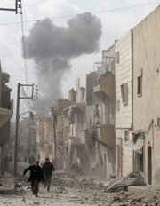 People run for cover following a reported air strike by Syrian government forces in the city of Aleppo last week. International officials reportedly are formulating a plan to destroy the Syrian government's chemical-arms production sites.
