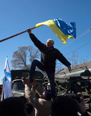 A pro-Russian protester takes down a Ukrainian flag as activists storm a Ukrainian air base in western Crimea on Saturday. The House Foreign Affairs Committee on Tuesday approved a Russia-sanctions bill with language that may lead to tightened penalties against Iran's supporters.