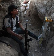 A Syrian rebel fighter sits in a trench during a Friday clash with government forces in the city of Deir Ezzor. An international operation to destroy Syria's chemical arms may miss a June deadline for completion, the head of a global watchdog agency said on Monday.