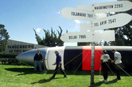Signs in the shape of missiles pointing the direction and distance to nuclear weapons-capable nations stand in front of a 50-foot mock missile set up by Greenpeace protesters outside Vandenberg Air Force Base, Calif., circa 2000, as a Minuteman 2 missile was being readied for test launch.