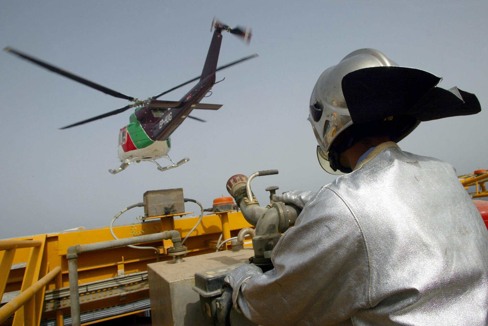 A technician works as a helicopter lands at an Iranian oil platform in the Persian Gulf in 2004. Iran appears poised for a fifth month to sell more oil than the average it is permitted to export under an interim nuclear deal with six world powers, according to observers.
