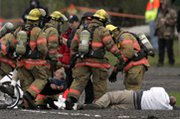"Firefighters respond to a simulated radiological ""dirty bomb"" attack during a 2007 drill in Portland, Ore. The White House is backing a plan to relax cleanup standards following such incidents, federal officials say in a draft report (AP Photo/Rick Bowmer)."