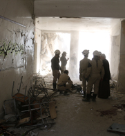 Syrian rescue workers stand inside a damaged Aleppo school following a reported government airstrike on Wednesday. U.S. officials said Syria's regime is refusing to relinquish chemical weapons over a standoff about how to handle one-time storage sites.