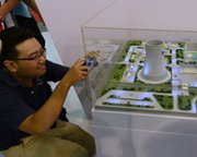 A student photographs a model of a Russian nuclear power plant on display at an international nuclear power exhibition held in Hanoi in October 2012. The White House is poised to submit a U.S.-Vietnamese nuclear trade agreement to Congress for review.