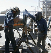 Metal workers weld together equipment at Iran's Arak heavy-water reactor complex in 2004. U.N. analysts reported an apparent drop in Tehran's efforts to obtain arms-usable materials in violation of international sanctions.
