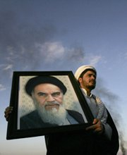 A man holds a picture of former Iranian supreme leader Ruhollah Khomeini during a 2005 demonstration at Iran's Natanz uranium-enrichment facility. Diplomats say they are tackling an entrenched uranium-enrichment standoff in talks over Iran's disputed nuclear activities