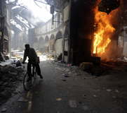 A bicyclist passes a burning building in the Syrian city of Homs on Monday. French Foreign Minister Laurent Fabius on Tuesday accused the government in Damascus of carrying out 14 or more chemical strikes since October 2013.