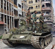 Syrian government troops stand on a tank in the city of Homs earlier this month. President Bashar Assad's forces reportedly launched an assault to clear a path for removing the regime's final declared chemical-weapon materials.