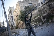 A Syrian opposition fighter fires at military troops in the city of Aleppo on Wednesday. The U.S. Defense Department projects it would need up to 75,000 troops to secure Syria's chemical arsenal, the New York Times reported (AP Photo/Narciso Contreras).