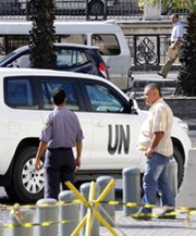 A U.N. vehicle departs from a Damascus hotel on Thursday. An international team on Friday prepared to begin eliminating Syrian chemical-weapon assets (Louai Beshara/Getty Images).