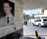 A poster of Syrian President Bashar Assad adorns a wall as a U.N. vehicle carrying inspectors from the Organization for the Prohibition of Chemical Weapons on Wednesday leaves a hotel in Damascus. OPCW personnel so far have traveled to three locations as part of an operation to eliminate Assad's chemical arsenal, a spokesman said on Thursday (Louai Beshara/AFP/Getty Images).