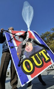 A South Korean activist holds a banner showing a portrait of North Korean leader Kim Jong Un at a park near the inter-Korean border in February. North Korean officials have offered in semi-formal talks with U.S. officials to abstain from new nuclear and missile tests if aid-for-denuclearization negotiations are resumed (Jung Yeon-je/AFP/Getty Images).