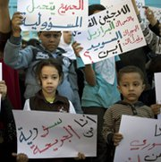 Children who fled civil-war-torn Syria on Monday hold placards during a protest in front of the United Nations Relief and Works Agency in Gaza city. The Syrian government, meanwhile, has submitted an official report detailing the contents of its chemical-weapons arsenal to international overseers (Mahmud Hams/Getty Images).