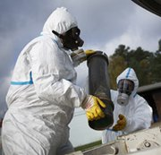 Employees in protective clothing on Wednesday conduct a demonstration at a German chemical-weapons disposal facility that the Organization for the Prohibition of Chemical Weapons uses as a reference laboratory. The organization on Thursday announced Syria completed the functional destruction of all critical equipment at its declared chemical-weapons production and mixing locations (Philipp Guelland/Getty Images).