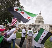 Waving the flag of the Syrian rebels, demonstrators opposed to the government of President Bashar Assad gather on the lawn of the U.S. Capitol on Monday,  as Congress prepares to debate President Obama's proposed military strike against Syria (AP Photo/J. Scott Applewhite).