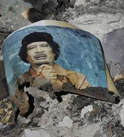A picture of former Libyan dictator Muammar Qadhafi is seen in the ashes during fighting in Libya in 2011. Two years after the uprising that led to the overthrow of the Libyan government, the country still has not begun eliminating thousands of pounds of mustard blister agent loaded in artillery rounds during the now-deceased leader's regime (AP Photo/Bela Szandelszky).