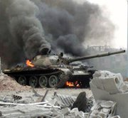 A Syrian government tank burns during a Wednesday clash with rebel fighters in a Damascus suburb. The Obama administration on Wednesday said it no longer expects Bashar Assad's regime to fully declare its chemical-warfare stocks this week (AP Photo/The Syrian Revolution Against Bashar Assad).