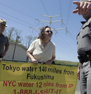 Protestor Marilyn Elie of Cortlandt Manor, N.Y., is escorted off the grounds of the Indian Point Energy Center in Buchanan, N.Y., in this May 2011 file photo. New York state officials want clarity on who would be responsible for cleaning up after a severe accident at a nuclear power plant, according to a recent legal filing with the Nuclear Regulatory Commission (AP Photo/Seth Wenig).