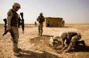 (Jul. 20) -U.S. and allied forces search a suspected arms cache during a village clearance operation in Iraq last week. The invasion of Iraq increased the extremist threat against the West, a former top British intelligence official said today (Warrick Page/Getty Images).