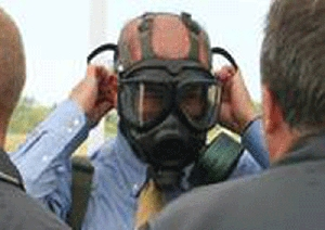 (Sep. 7) -Organization for the Prohibition of Chemical Weapons chief Ahmet Üzümcü, shown last week putting on a protective mask before entering a VX nerve agent storage igloo at the Blue Grass Army Depot in Kentucky. Üzümcü expressed hope that additional Middle Eastern countries could be persuaded to join the international chemical weapons ban (Organization for the Prohibition of Chemical Weapons photo).