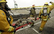 "(Oct. 7) -Firefighters evacuate a victim from the scene of a mock radiological ""dirty bomb"" attack during a 2004 drill at the Port of Los Angeles. The United States lacks adequate preparations for a radiological event, Representative Jane Harman (D-Calif.) said yesterday (David McNew/Getty Images)."