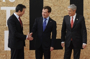 (Nov. 24) -NATO Secretary General Anders Fogh Rasmussen, left, shakes hands Saturday with Russian President Dmitry Medvedev at the alliance summit in Portugal. NATO states at the meeting put off a decision on further pullbacks of U.S. tactical nuclear weapons in Europe (Pierre-Philippe Marcou/Getty Images).