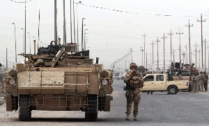 (Jun. 27) -British military personnel, left, and Iraqi troops in 2009 block a road in Basra, Iraq, following the detonation of a roadside bomb. A one-time senior British official recommended use of a 2002 report to mislead the country on prewar Iraq's WMD capabilities, a newly released document reveals (Essam al-Sudani/Getty Images).