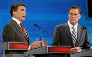 (Sep. 23) -Texas Governor Rick Perry, left, speaks as former Massachusetts Governor Mitt Romney listens during a Republican presidential debate on Thursday in Orlando, Fla. Perry said the United States should forge stronger ties with India in advance of any potential crisis in Pakistan in which Islamist extremists gain control of nuclear weapons (Phelan Ebenhack/Getty Images).