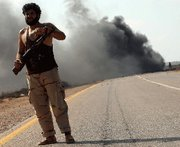 (Sep. 28) -A Libyan Transitional National Council fighter takes position in front of a burning truck near the front line in the suburbs of Sirte on Tuesday. NATO pressed Libya's new government to take steps toward destroying the nation's remaining chemical warfare stockpile and atomic substances (Ahmad al-Rubaye/Getty Images).